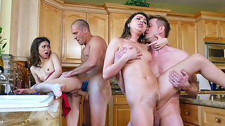 Two couples are having fun together in the kitchen